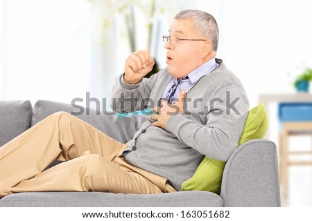 Mature man seated on a sofa coughing because of pulmonary disease at home - stock photo
