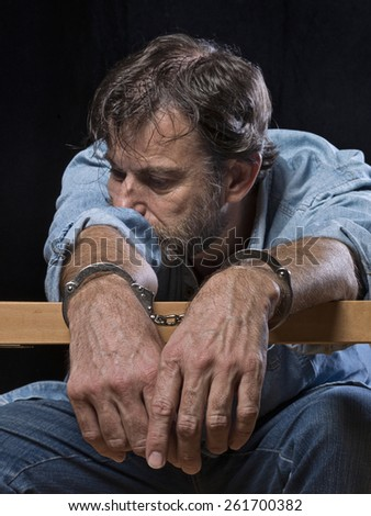 Mature man, sitting and depressed, with handcuffs - stock photo