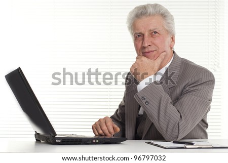 mature man sitting at the computer on a white background