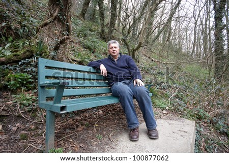 Mature man sitting on a park bench - stock photo