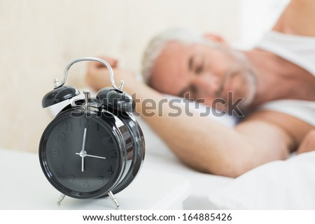 Mature man sleeping in bed with alarm clock in foreground at bedroom