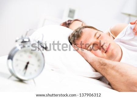 Mature man sleeping in bed with his wife
