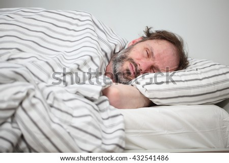 Mature man sleeping in his bed