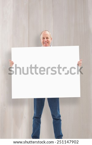 Mature man smiling at camera and holding card against bleached wooden planks background - stock photo