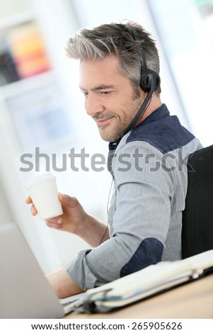 Mature man teleworking from home with laptop  - stock photo