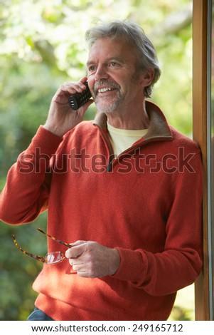 Mature Man Using Cordless Phone At Home - stock photo