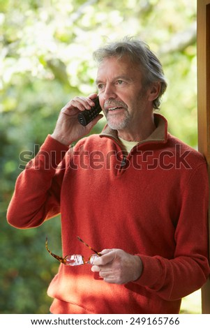 Mature Man Using Cordless Phone At Home - stock photo