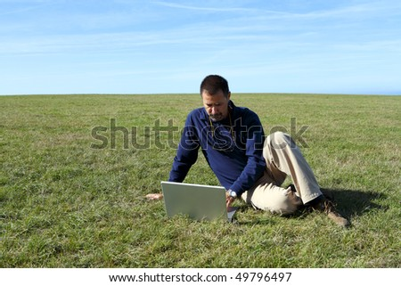Mature man using laptop in field - stock photo