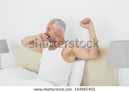 Mature man waking up in bed and stretching his arms at home