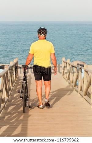 Mature man walking towards the beach carrying his bike - stock photo