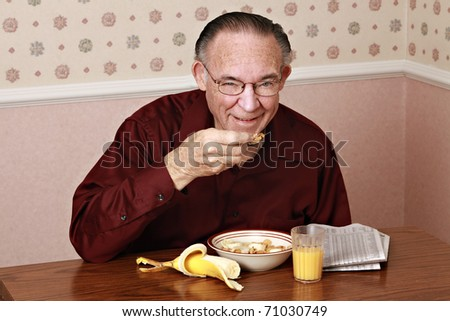 Mature man wearing maroon shirt eating cereal for breakfast.