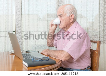 Mature man with a laptop and cup of coffee - stock photo