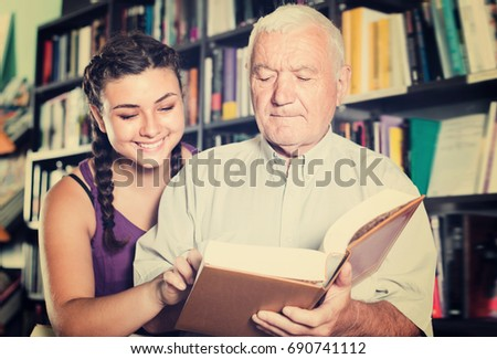 Mature man with adult girl are reading books in bookstore
