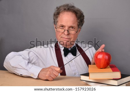 Mature man with books acting as a teacher/Mature Teacher/Man is a mature teacher character - stock photo