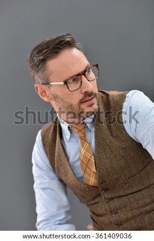 Mature man with eyeglasses standing on grey background - stock photo