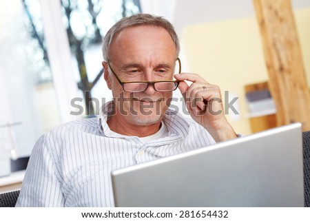 mature man with laptop and eyeglasses - stock photo