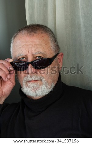 mature man with sunglasses dressed in black