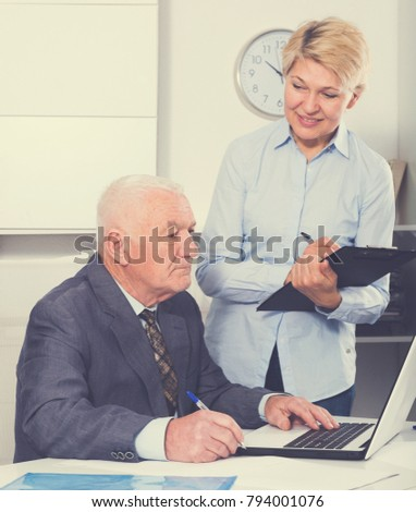 Mature manager and secretary having productive day at work in office