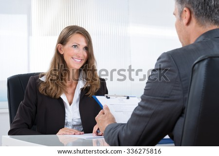 Mature Manager Interviewing A Female Applicant In Office
