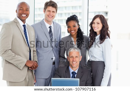 Mature manager smiling with a laptop and his business team - stock photo
