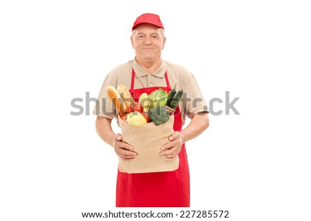 Mature market vendor holding a grocery bag isolated on white background - stock photo
