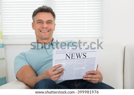 Mature Mature Man Reading Newspaper Sitting On Sofa - stock photo