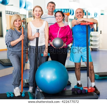 Mature men and women after exercising in  gym with sport equipment - stock photo