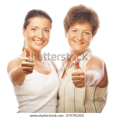 Mature mother and attractive daughter hugging  showing thumb up - stock photo