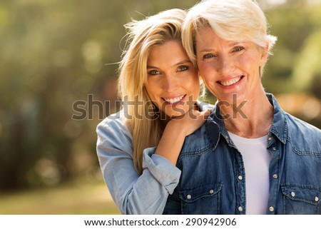 mature mother and young daughter looking at the camera - stock photo