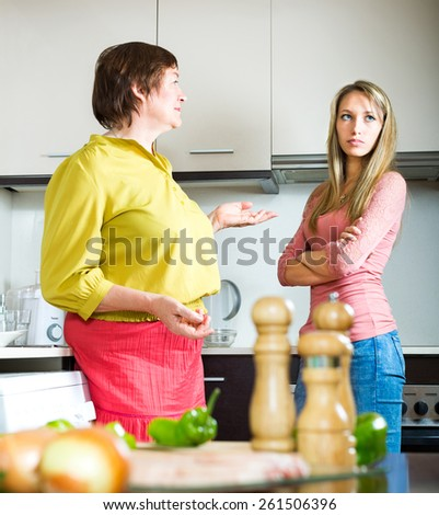 Mature mother arguing in the kitchen with her â??â??adult daughter - stock photo