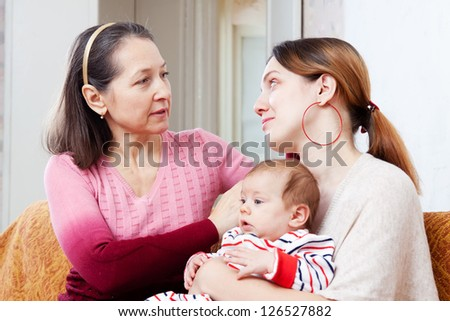 Mature mother gives solace to crying adult daughter with baby at home - stock photo