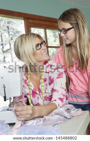 Mature mother looking at daughter while sewing cloth - stock photo