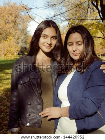 mature mother with daughter outside in park - stock photo