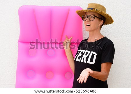 Mature nerd tourist woman holding air mattress while she is looking worried that it might start to rain soon