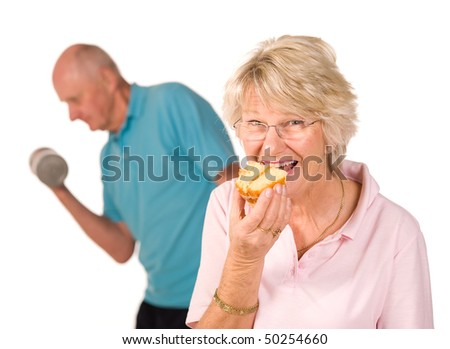 Mature older lady having a cheeky slice of cake with men working out at the gym - stock photo
