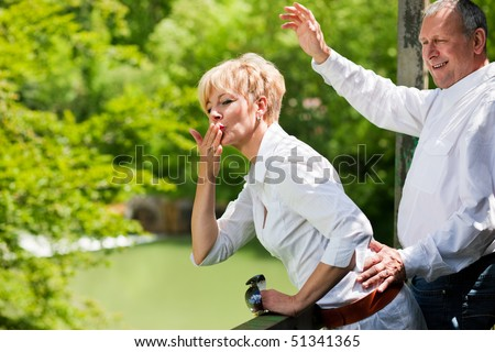 Mature or senior couple at a summer day standing on a bridge waving their hands as if to say goodbye to somebody - stock photo