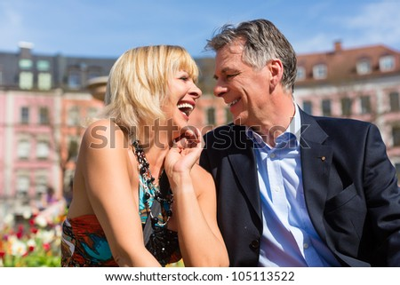Mature or senior couple sitting on a bench during spring in the city and enjoy the sun - stock photo