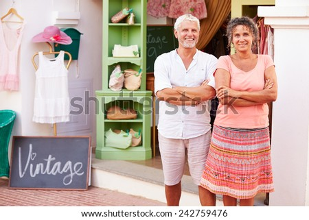 Mature Owners Of Fashion Store Standing Outside Shop - stock photo