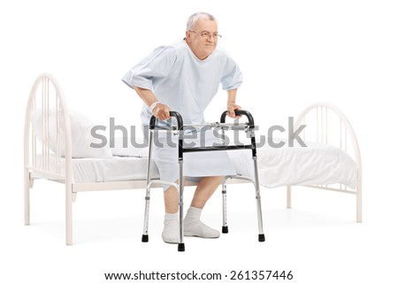 Mature patient getting up from bed with walker isolated on white background - stock photo
