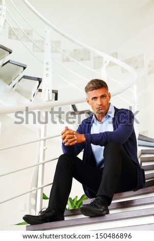 Mature pensive man sitting on stairs at home - stock photo