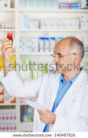 mature pharmacist with glases controlling medicine, holding prescription - stock photo
