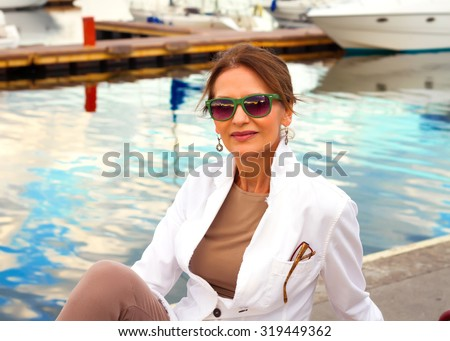 Mature pretty woman wearing white jacket and beige clothes,enjoying a relaxed sunny day out at a marina, with boats as background, with blue sky as copy space.Beautiful sunset at the yacht club - stock photo