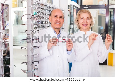 Mature professional opticians standing near display with spectacles and smiling. Focus on man