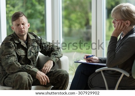 Mature psychologist talking with despair young soldier - stock photo