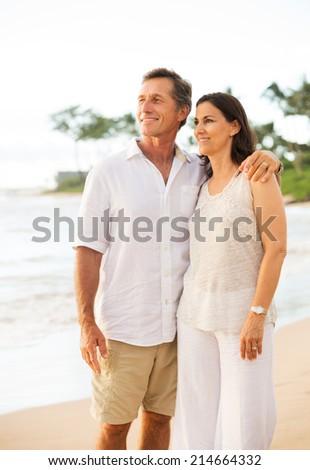 Mature Retired Couple Enjoying Sunset on Beach Vacation - stock photo