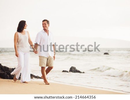 Mature Retired Couple Enjoying Sunset Walk on the Beach - stock photo