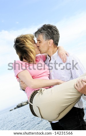 Mature romantic couple of baby boomers kissing on a beach - stock photo