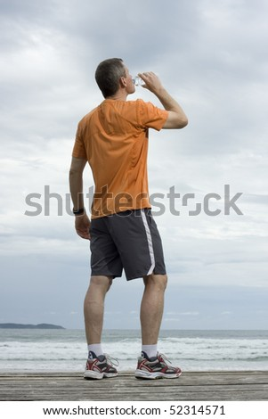 Mature runner drinking water on a beach - stock photo