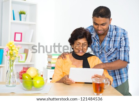 Mature 50s Indian woman and son using digital computer tablet at home - stock photo