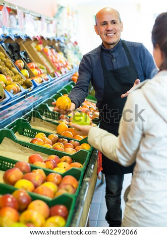 Mature salesman offering caucasian female customer good price for fruits